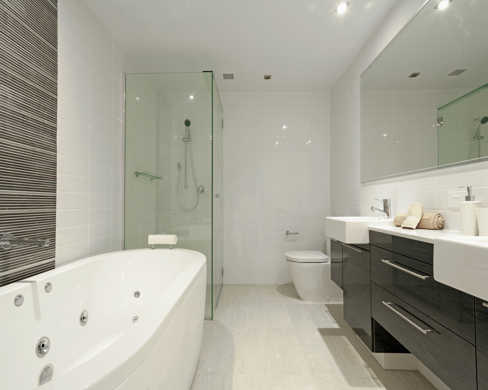Stylish twin bathroom with two sinks, mirror, shower, toilet and round bathtub.